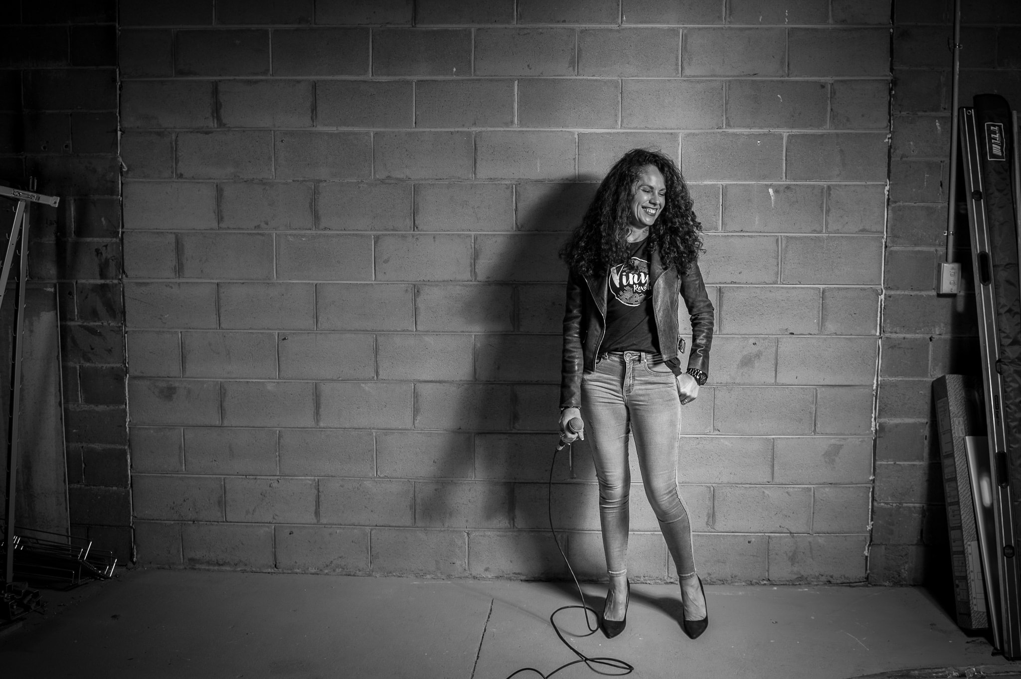 A female singer smiles with a microphone in front of a cinderblock wall